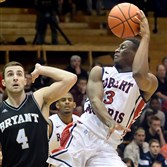 Robert Morris' Kavon Stewart passes the ball off in front of Bryant's Shane McLaughlin in the second half of the semi-finals of the NEC tournament at the Sewall Center.