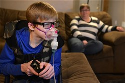 Mikey Dugan, 13, plays video games while receiving his breathing treatment and chest physical therapy March 6 at home in West Mifflin.