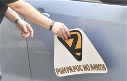 An employee of Yellow Cab attaches one of the magnetic signs for the YellowZ cab service, which can be summoned with an online app, to a car.