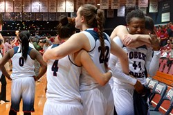 Robert Morris women's basketball players console each as St. Francis Brooklyn celebrates. The Colonials lost in the NEC Championship game at the Sewell Center at Robert Morris in Moon.