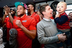 Robert Morris teammates Lucky Jones, Aaron Tate and head coach Andy Toole, with his son, Ryan, react after learning they will face North Florida Wednesday in a NCAA play-in game in Dayton.