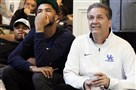 Kentucky basketball players Aaron Harrison, back left, Andrew Harrison and head coach John Calipari watch the NCAA tournament selection show at Calipari's home in Lexington, Ky.