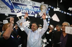 Israeli Likud Party supporters react to the exit polls while they wait for the announcement of the first official results of Israel's parliamentary elections Tuesday.