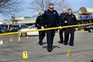 Police investigate the scene of a shootout in the parking lot of the Edgewood Town Center on Thursday.