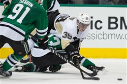 Penguins left wing David Perron jumps over Dallas's defenseman Alex Goligoski to get the puck during the third period Thursday at the American Airlines Center in Dallas. The Stars defeated the Penguins 2-1.