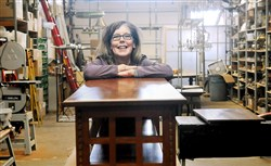 Kate Joyce poses on one of her early tables which sits in her workshop in preparation for refinishing.