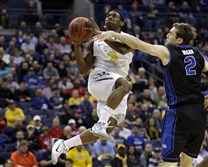 West Virginia's Juwan Staten (3) goes in for a shot against Buffalo's Will Regan (2) in the first half of an NCAA tournament game in the Round of 64 in Columbus.