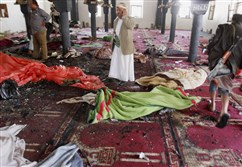 People stand amid bodies covered with blankets Friday in a mosque after a suicide attack during the noon prayer in Sanaa, Yemen. Triple suicide bombers hit a pair of mosques crowded with worshippers in the capital on Friday, causing heavy casualties.