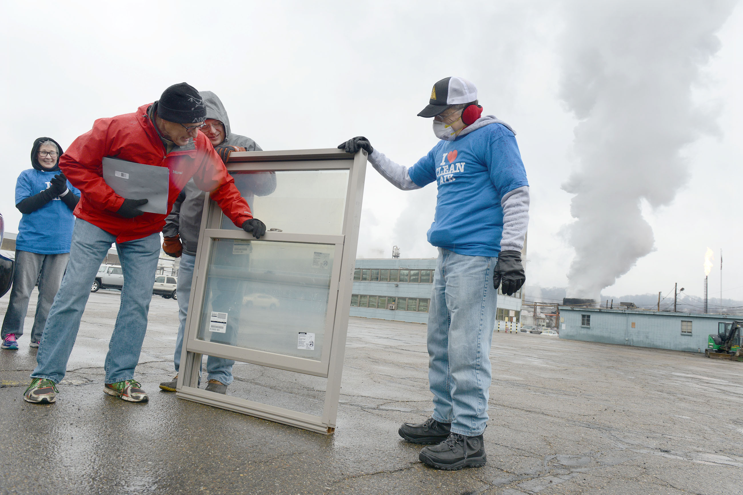"20150320ppShenango1LOCAL Tom Hoffman with the Western Pennsylvania Clean Water Action closes the window for the ""First Annual Closed Window Award"" during a protest near the entrance of the Shenango Coke Works on Neville Island while steam rises to the sky in the background as ""quenching"" — cooling off the coke — rises from the plant. Residents from the North Boroughs and the city of Pittsburgh affected by air pollution from the plant presented the award to emphasize the chronic history of failing to meet air quality standards. Holding the window are Angelo Taranto (right) from Ross Township and Randy Francisco with the Sierra Club."