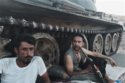 Members of a militia group loyal to Yemen's President Abed Rabbo Mansour Hadi, known as the Popular Committees, chew qat, Yemen's favorite drug, as they sit next to their tank, guarding a major intersection in Aden, Yemen, Saturday, March 21, 2015. Yemen's Shiite rebels issued a call to arms Saturday to battle forces loyal to the embattled President Hadi, as U.S. troops evacuated a southern air base over al-Qaida militants seizing a nearby city, authorities said. (AP Photo/Hamza Hendawi)