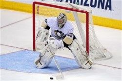 Penguins goalie Marc-Andre Fleury looks to pass the puck in the first period Saturday against the Coyotes in Glendale, Ariz.