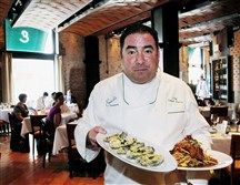 Chef Emeril Lagasse poses with Oysters Julia and Andouille Crusted Redfish, left, and Darian's Chicken & Waffles, right, at  Emeril's Restaurant in New Orleans.