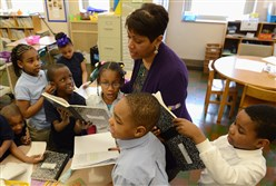 Students in Shamira Underwood's second grade class at Pittsburgh's Lincoln PreK-5 School swarm principal Virginia Hill with their writing workbooks during a visit to the class.