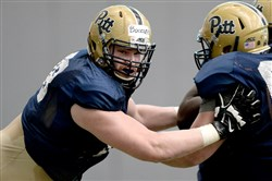 Pitt's Alex Bookser works with Aaron Reese during spring camp on the South Side yesterday afternoon.