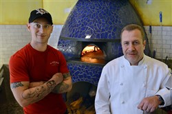 Kevin Konn, left, and executive chef Richie Sphatt stand at the hand-built, wood-fired pizza oven at Il Pizzaiolo in Market Square.