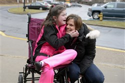 Tracy Montgomery and her daughter, Kaitlin, 10, arrive at a Steel Valley School Board meeting last month.