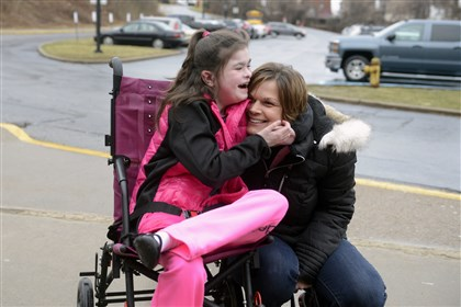 Tracy Montgomery arrives at the Steel Valley school board meeting on Thursday with her daughter Kaitlin, who has chronic lung disease and pulmonary hypertension, foot problems and autism.