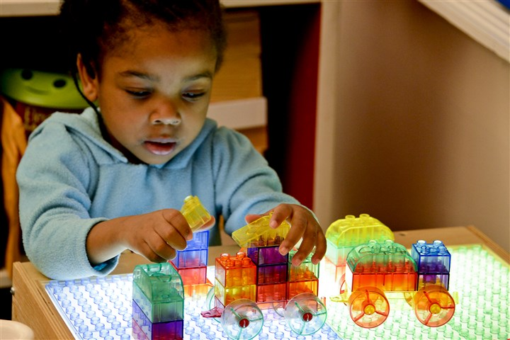 20150326dsEarlyChildhoodLocal03-1 Syleena Fraizer, 3, uses a light table to build in Flo Monroe's preschool class at the Conroy Education Center's early childhood program on the North Side.