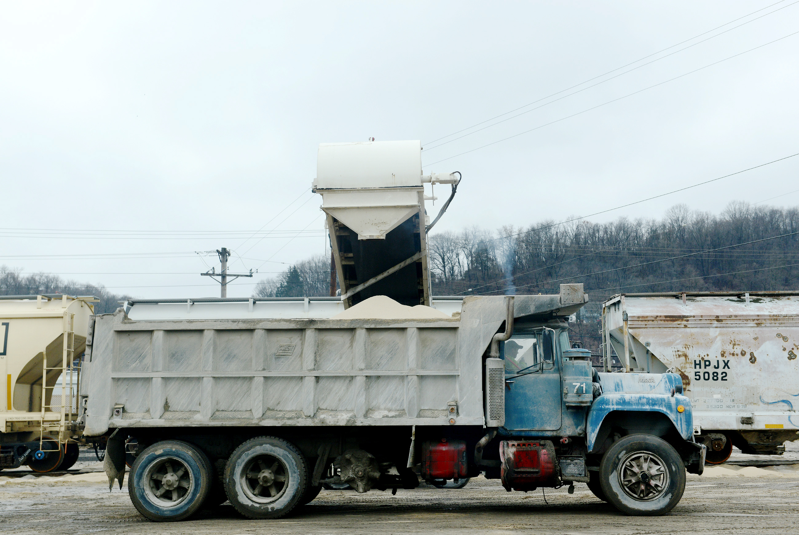 20150320MWHmrieBiz02-1 Sand, used by drillers during the hydraulic fracturing process to prop open cracks in the ground to extract natural gas from the Marcellus and Utica shale plays, is loaded onto a truck after it is filtered at McKees Rocks Industrial Enterprises. The company sees more than 50,000 truckloads leave its facilities each year.