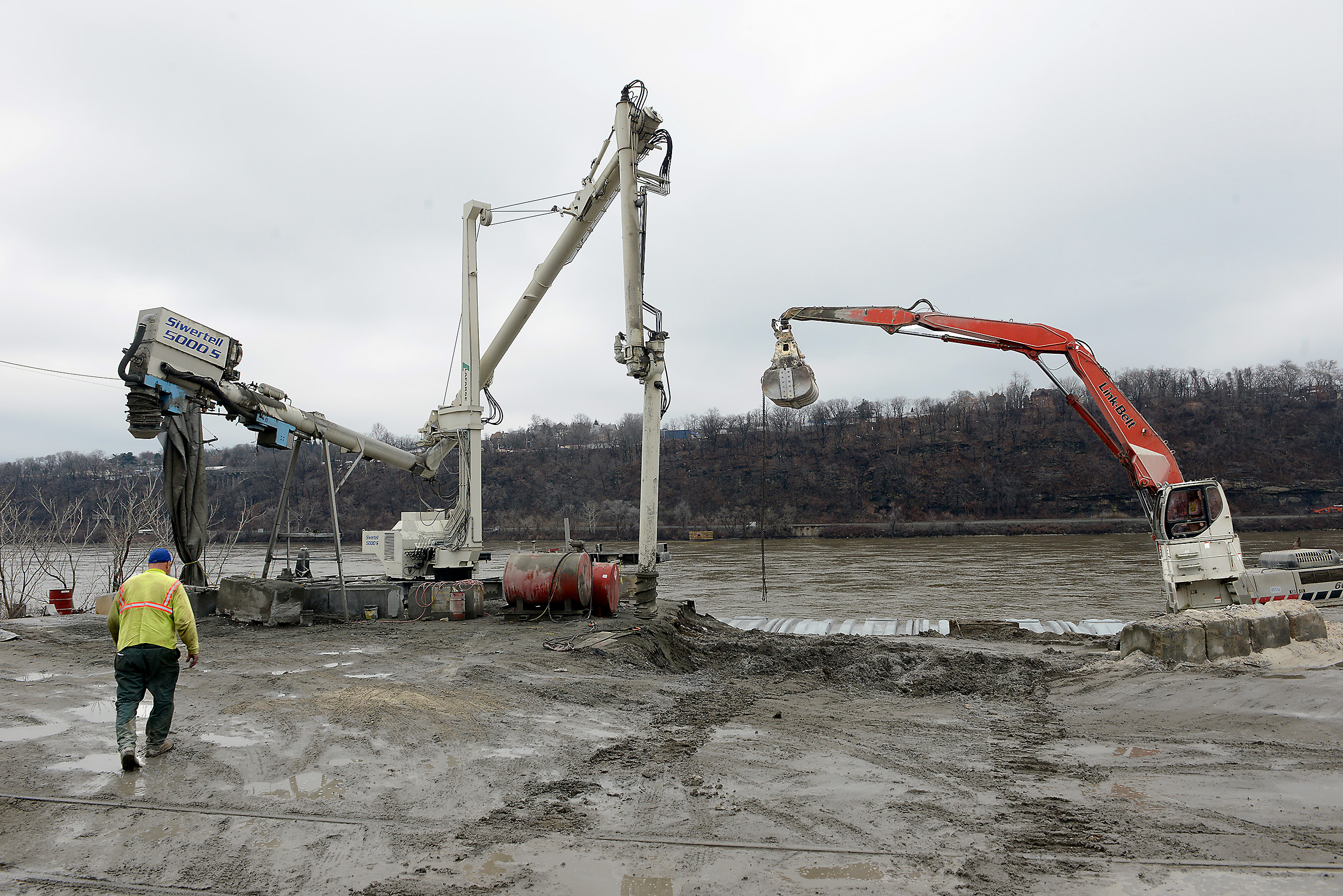 20150320MWHmrieBiz05-4 Michael Henninger/Post-Gazette 20150320 mrie Biz 03/20/2015 Equipment used to unload barges rest at the edge of the Ohio River at McKees Rocks Industrial Enterprises. An auger, left, and a Link-Belt excavator, right are used to process and move sand from incoming barges.
