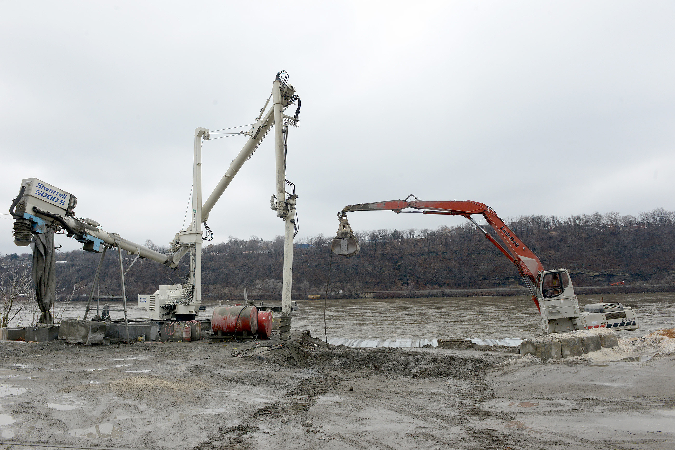20150320MWHmrieBiz06-5 Michael Henninger/Post-Gazette 20150320 mrie Biz 03/20/2015 Equipment used to unload barges rest at the edge of the Ohio River at McKees Rocks Industrial Enterprises. An auger, left, and a Link-Belt excavator, right are used to process and move sand from incoming barges.