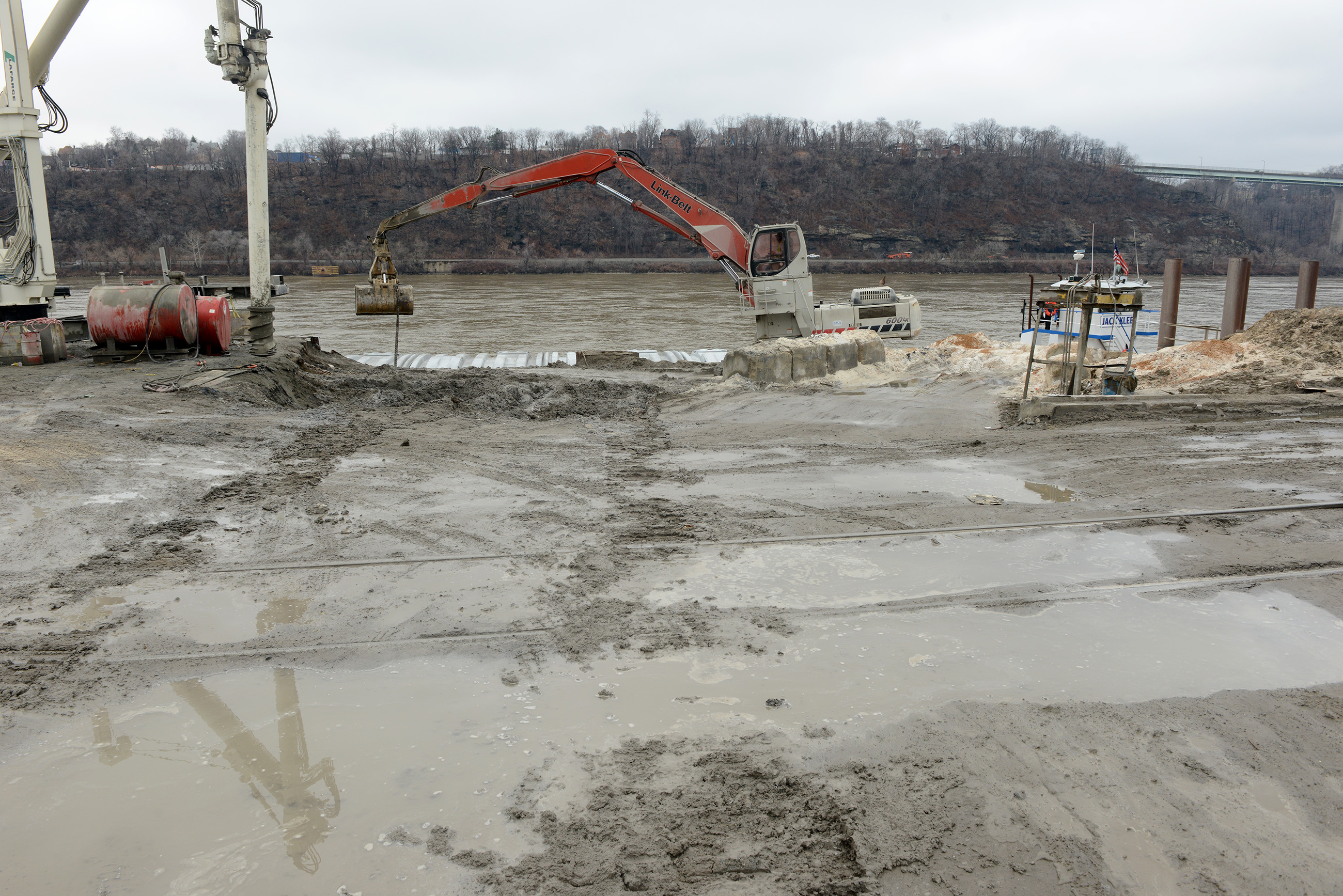 20150320MWHmrieBiz07-6 Michael Henninger/Post-Gazette 20150320 mrie Biz 03/20/2015 Equipment used to unload barges rest at the edge of the Ohio River at McKees Rocks Industrial Enterprises. An auger, left, and a Link-Belt excavator, right are used to process and move sand from incoming barges.