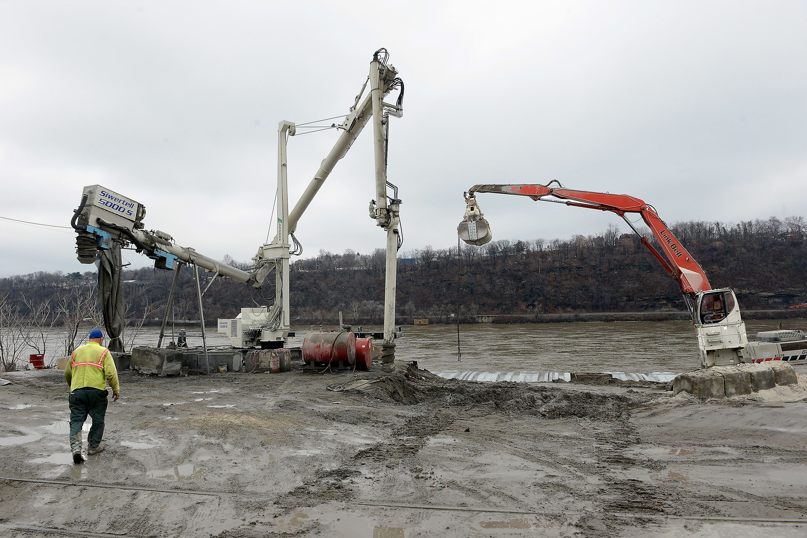 20150320MWHmrieBiz05-4 Equipment used to unload barges rests at the edge of the Ohio River at McKees Rocks Industrial Enterprises. An auger, left, and a Link-Belt excavator, right are used to process and move sand from incoming barges.