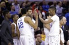 Kentucky players celebrate after a 78-39 win over West Virginia in a college basketball game in the NCAA men's tournament regional semifinals in Cleveland.