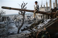 A Syrian Kurdish boy sits on a destroyed tank Friday in the Syrian town of Kobane, also known as Ain al-Arab.