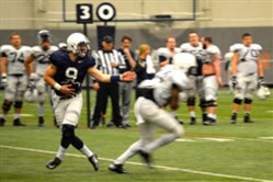 Backup quarterback Trace McSorley hands the ball off during situational drills Saturday afternoon.