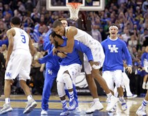 Kentucky players celebrate after a 68-66 win over Notre Dame in a college basketball game in the NCAA men's tournament regional finals, Saturday, March 28, 2015, in Cleveland.