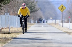 A cyclist rides the Armstrong Trail through Ford City on a chilly, sunny Sunday.
