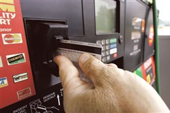 A customer swipes his credit card at a gas station pump in Morganton, N.C.