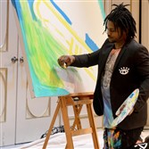 Baron Batch creates a painting during the Arts & Drafts event.