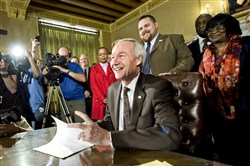Arkansas Gov. Asa Hutchinson signs a reworked religious freedom bill into law after it passed in the House at the Arkansas state Capitol in Little Rock, Ark., Thursday.
