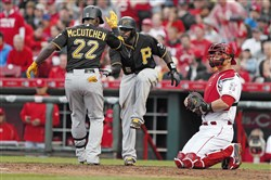 Andrew McCutchen is congratulated at home plate by Josh Harrison after hitting a two-run home run off Reds starting pitcher Kevin Gregg during the eighth inning of Monday's game.