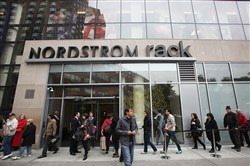 Shoppers wait in line to enter on opening day of the new Nordstrom Rack store in New York City in May 2010.