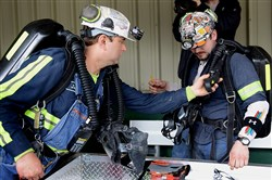 Mine rescue workers check teammates' emergency breathing packs as they prepare to enter Consol Energy's Harvey Mine for a rescue drill Wednesday to test the Mine Safety and Health Administration's (MSHA) new Mine Emergency Operations system.