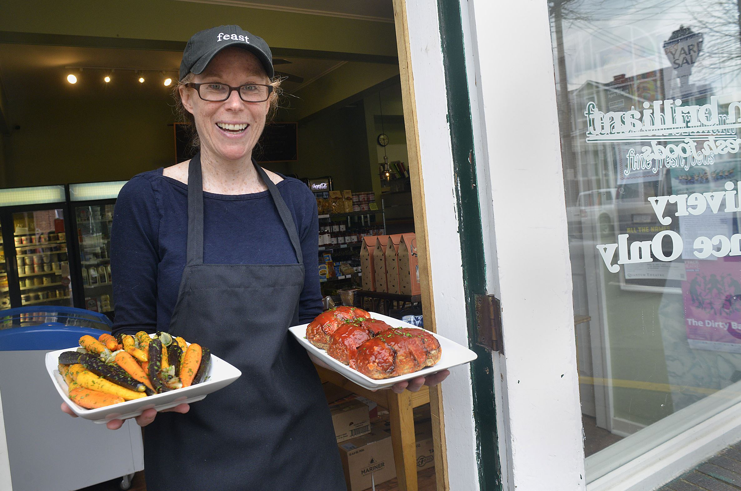 20150409lrbrilliantfood09-7 Patty Danforth , the propretor of Feast on Brilliant in Aspinwall, poses in the doorway with two of the prepared items sold at the grocery, herbed carrots and meatloaf.