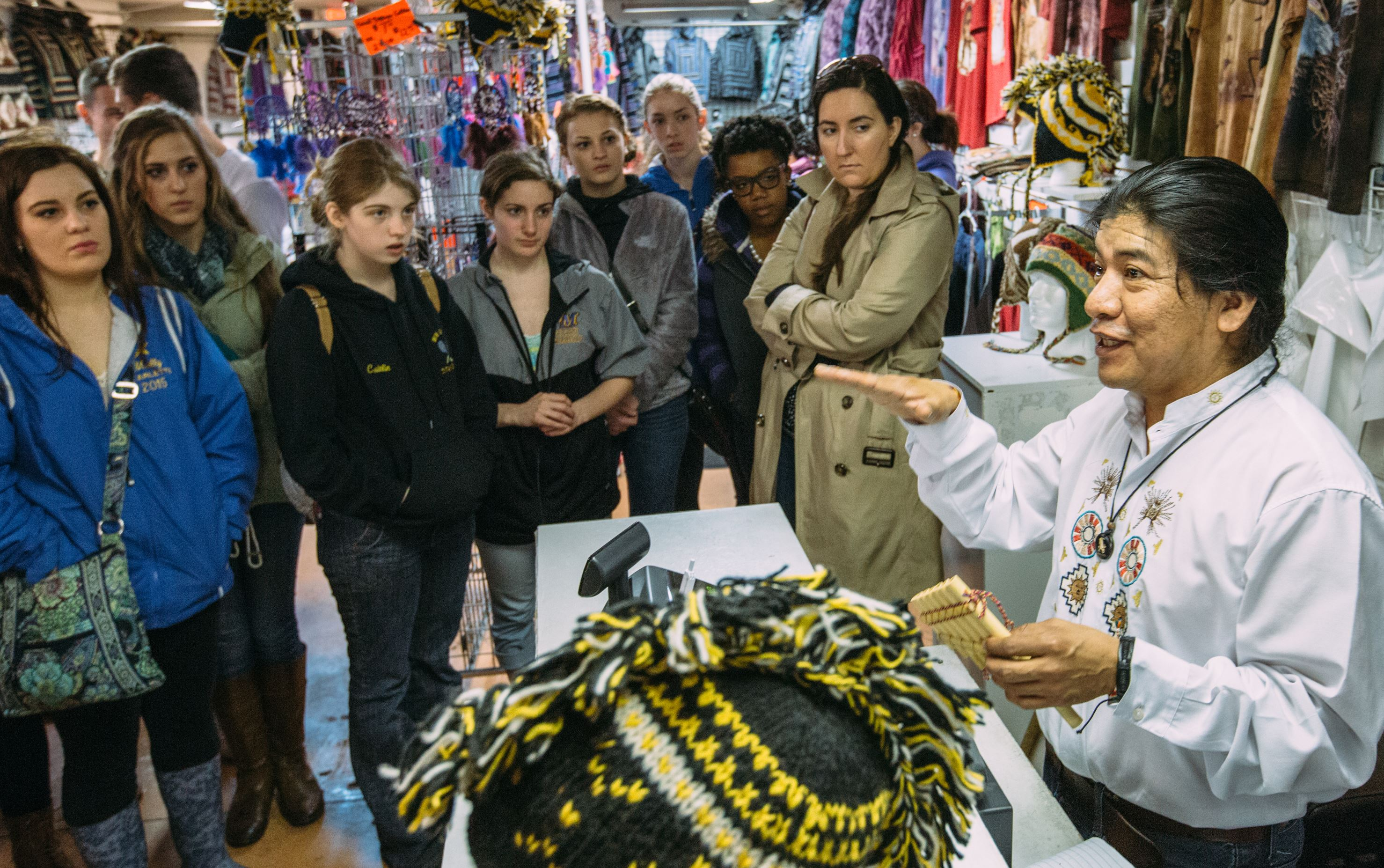 20150410ARSpanishTourFood2-6 A group of students from West Mifflin Area High School listen to Patricio Moran, of Native Inka's Shop, during a field trip in the Strip District.