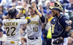 The Pirates' Andrew McCutchen is congratulated by teammate Jordy Mercer after hitting a three-run home run during the sixth inning. The Brewers' Martin Maldonado looks on.