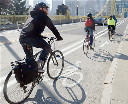 Bicyclists head to Downtown Pittsburgh using the bike lanes installed last spring on the Roberto Clemente Bridge.