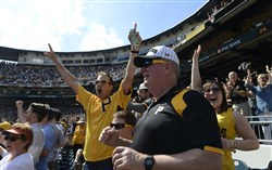 Dan Nagy, left, of High Point, N.C., and his father, Bill Nagy, celebrate a home run by Pedro Alvarez in the seventh inning, during the Pirates home opener against the Detroit Tigers at PNC Park Monday.