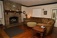 The living room with original fireplace and leaded glass doors in the two-bedroom apartment in the home for sale in Cheswick. The house has four apartments and a boutique. The home was once the borough building.