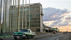 An Amer­i­can clas­sic car drives past the build­ing of the U.S. In­ter­ests Sec­tion in Ha­vana, Cuba.