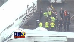 In this frame from video, workers walk with a Menzies Aviation cargo worker after the worker was removed from the cargo hold of an Alaska Airlines passenger airplane on Monday at Seattle-Tacoma International Airport in Seattle.