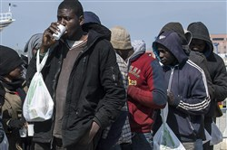 Rescued migrants line up Wednesday after disembarking at the southern Italian port of Corigliano, Italy.