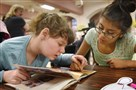 Amber Bufalini, 14, left, a student at the Children's Institute of Pittsburgh, gets some reading help Friday from Monica Brunner, 13, an eighth-grader at Assumption School.