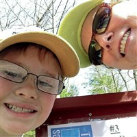Smile! Patti Jac­o­bina and Logan Jac­o­bina, 9, of Li­go­inier pro­vide proof of place by mug­ging for a cellp­hone cam­era in front of a trail-side sign at Linn Run.