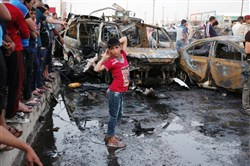 A boy watches as people and security forces gather at the scene of a car bomb explosion in Habibya in eastern Baghdad on Friday. A series of bombings ripped through Baghdad Friday, mainly targeting public places and killing and wounding civilians, officials said.